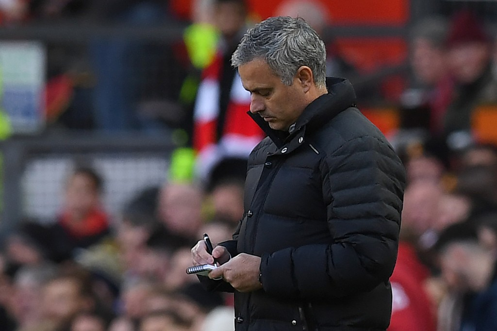 Manchester United's Portuguese manager Jose Mourinho makes notes as he watches his players from the touchline during the English Premier League football match between Manchester United and Arsenal at Old Trafford in Manchester, north west England, on November 19, 2016. / AFP / PAUL ELLIS / RESTRICTED TO EDITORIAL USE. No use with unauthorized audio, video, data, fixture lists, club/league logos or 'live' services. Online in-match use limited to 75 images, no video emulation. No use in betting, games or single club/league/player publications. / (Photo credit should read PAUL ELLIS/AFP/Getty Images)