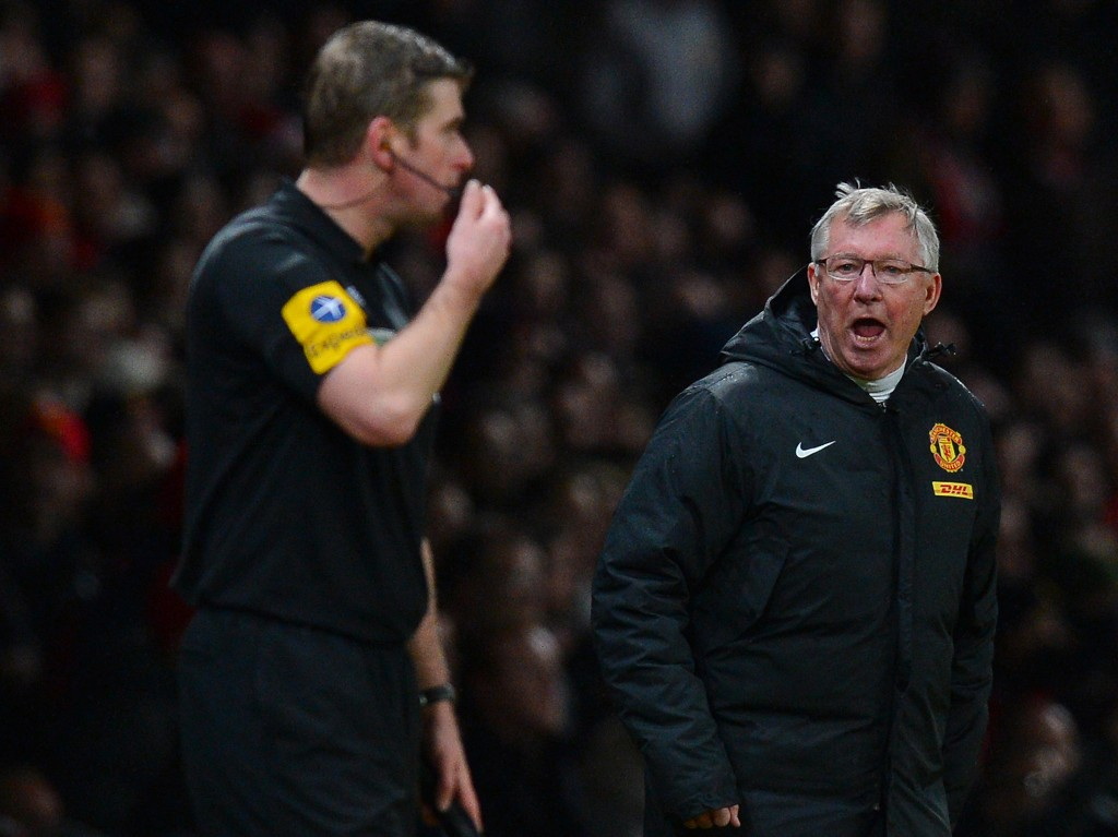 """Manchester United's Scottish manager Alex Ferguson (R) shouts at assistant referee Jake Collin (L) during the English Premier League football match between Manchester United and Newcastle United at Old Trafford in Manchester, north-west England on December 26, 2012. AFP PHOTO/ANDREW YATES RESTRICTED TO EDITORIAL USE. No use with unauthorized audio, video, data, fixture lists, club/league logos or """"live"""" services. Online in-match use limited to 45 images, no video emulation. No use in betting, games or single club/league/player publications (Photo credit should read ANDREW YATES/AFP/Getty Images)"""