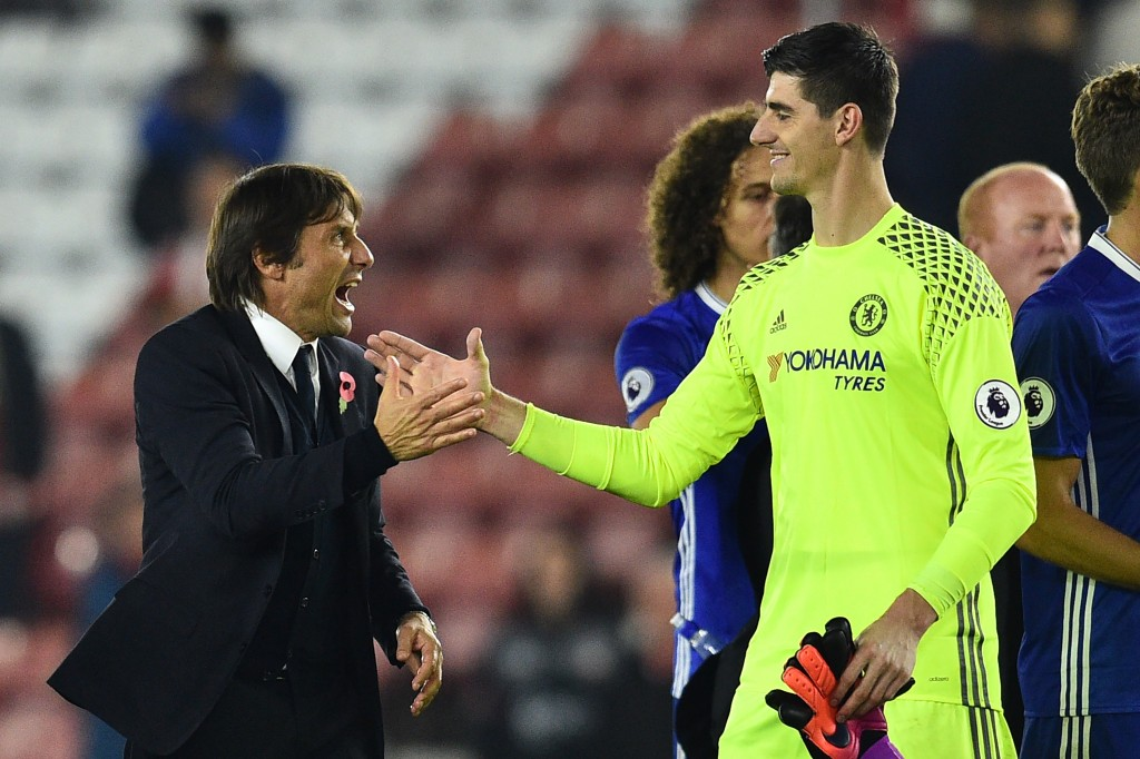 Chelsea's Italian head coach Antonio Conte (L) celebrates with Chelsea's Belgian goalkeeper Thibaut Courtois on the pitch after the English Premier League football match between Southampton and Chelsea at St Mary's Stadium in Southampton, southern England on October 30, 2016. Chelsea won the game 2-0. / AFP / GLYN KIRK / RESTRICTED TO EDITORIAL USE. No use with unauthorized audio, video, data, fixture lists, club/league logos or 'live' services. Online in-match use limited to 75 images, no video emulation. No use in betting, games or single club/league/player publications. / (Photo credit should read GLYN KIRK/AFP/Getty Images)