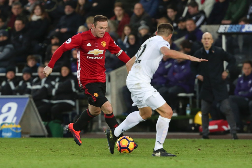 Manchester United's English striker Wayne Rooney (L) vies with Swansea City's Spanish defender Angel Rangel during the English Premier League football match between Swansea City and Manchester United at The Liberty Stadium in Swansea, south Wales on November 6, 2016. / AFP / GEOFF CADDICK / RESTRICTED TO EDITORIAL USE. No use with unauthorized audio, video, data, fixture lists, club/league logos or 'live' services. Online in-match use limited to 75 images, no video emulation. No use in betting, games or single club/league/player publications. / (Photo credit should read GEOFF CADDICK/AFP/Getty Images)