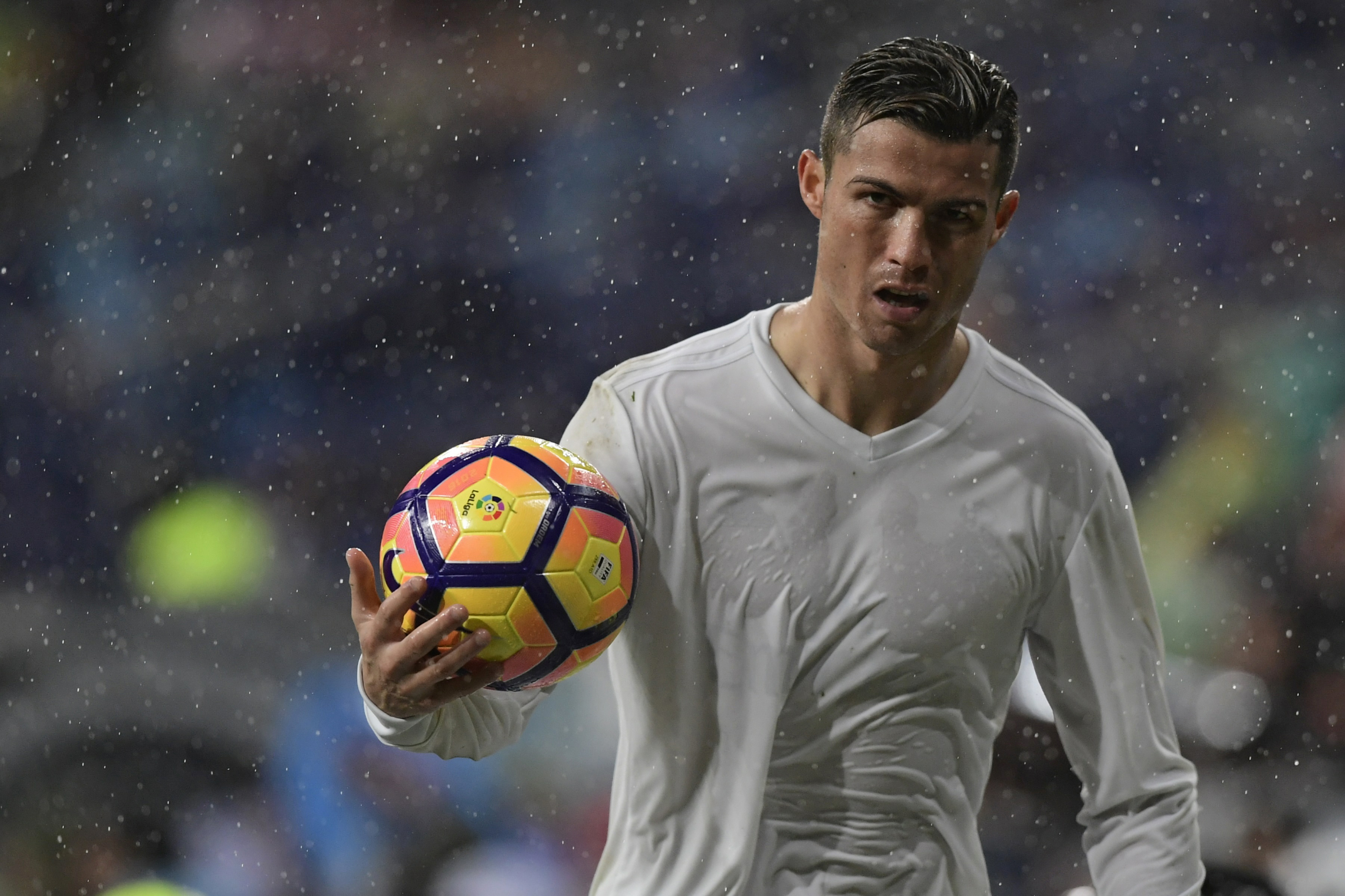 Real Madrid's Portuguese forward Cristiano Ronaldo holds a ball during the Spanish league football match Real Madrid CF vs Sporting de Gijon SAD at the Santiago Bernabeu stadium in Madrid on November 26, 2016. / AFP / JAVIER SORIANO (Photo credit should read JAVIER SORIANO/AFP/Getty Images)