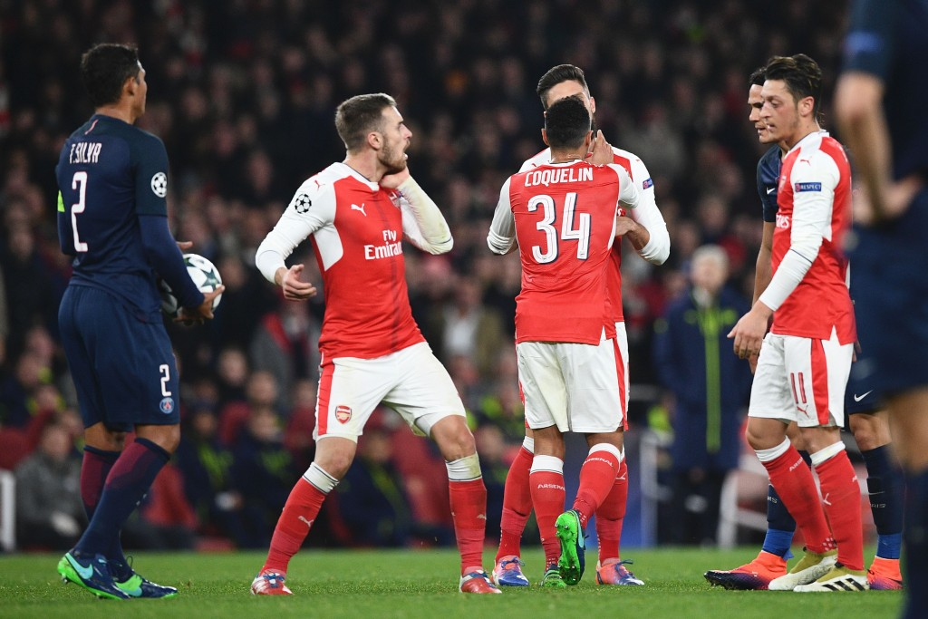 Arsenal's Welsh midfielder Aaron Ramsey (2L) puts his hand to his cheek after a scuffle with Paris Saint-Germain's Uruguayan forward Edinson Cavani (2R) after Arsenal were awarded a penalty during the UEFA Champions League group A football match between Arsenal and Paris Saint-Germain at the Emirates Stadium in London on November 23, 2016. / AFP / Justin TALLIS (Photo credit should read JUSTIN TALLIS/AFP/Getty Images)