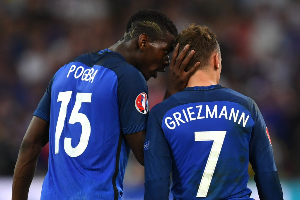 France's midfielder Paul Pogba (L) celebrates with France's forward Antoine Griezmann who scored a penalty shot giving France the first goal of the match during the Euro 2016 semi-final football match between Germany and France at the Stade Velodrome in Marseille on July 7, 2016. / AFP / PATRIK STOLLARZ (Photo credit should read PATRIK STOLLARZ/AFP/Getty Images)