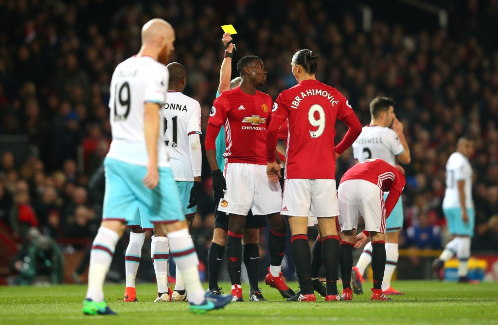 MANCHESTER, ENGLAND - NOVEMBER 27: Paul Pogba of Manchester United (C) is shown a yellow card during the Premier League match between Manchester United and West Ham United at Old Trafford on November 27, 2016 in Manchester, England. (Photo by Alex Livesey/Getty Images)