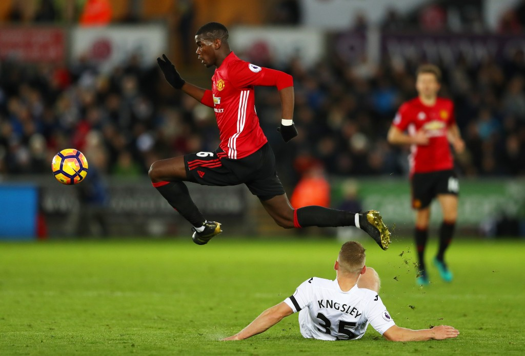 SWANSEA, WALES - NOVEMBER 06: Stephen Kingsley of Swansea City attempts to tackle Paul Pogba of Manchester United during the Premier League match between Swansea City and Manchester United at Liberty Stadium on November 6, 2016 in Swansea, Wales. (Photo by Michael Steele/Getty Images)
