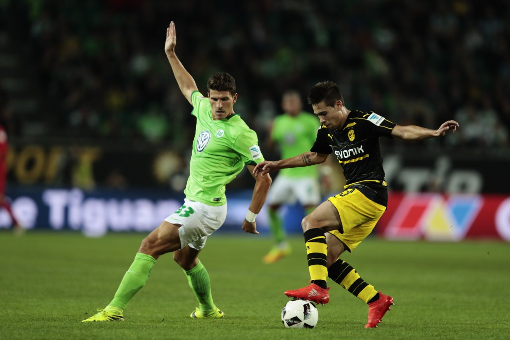 WOLFSBURG, GERMANY - SEPTEMBER 20: Mario Gomez (L) of Wolfsburg and Raphael Guerreiro (R) of Dortmund compete for the ball during the Bundesliga match between VfL Wolfsburg and Borussia Dortmund at Volkswagen Arena on September 20, 2016 in Wolfsburg, Germany. (Photo by Oliver Hardt/Bongarts/Getty Images)