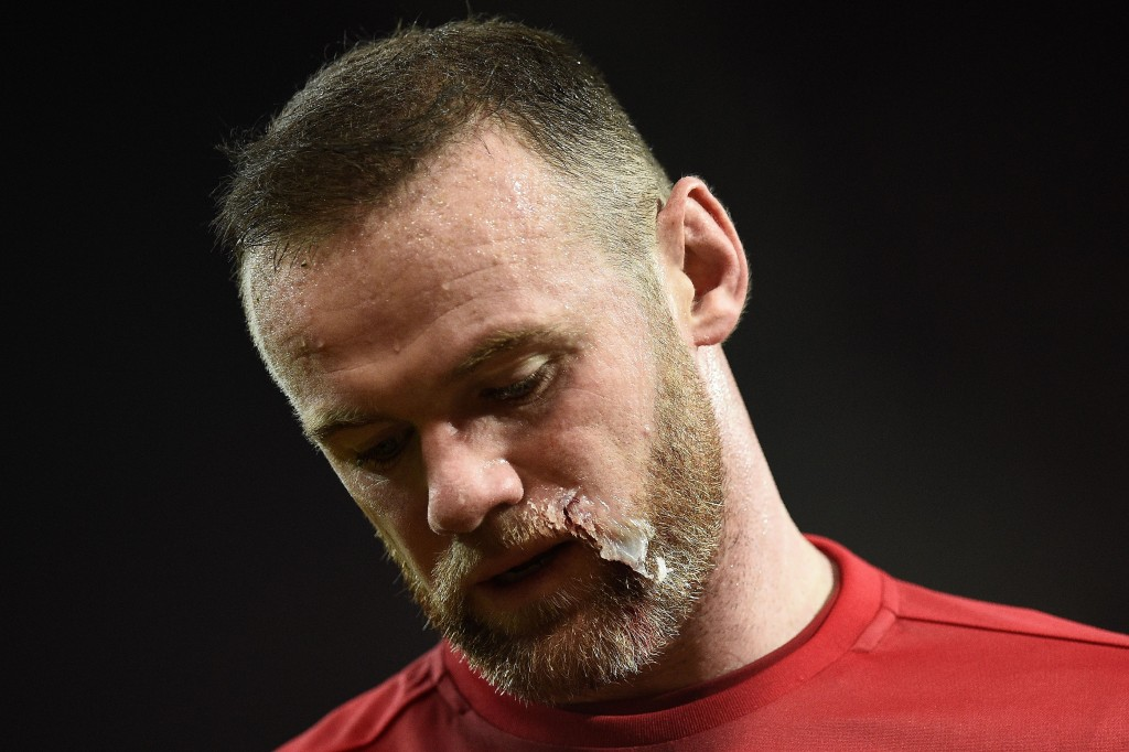 Manchester United's English striker Wayne Rooney returns to the pitch after having treatment to his face during the EFL (English Football League) Cup quarter-final football match between Manchester United and West Ham United at Old Trafford in Manchester, north west England, on November 30, 2016. (Photo by Oli Scarff/AFP/Getty Images)