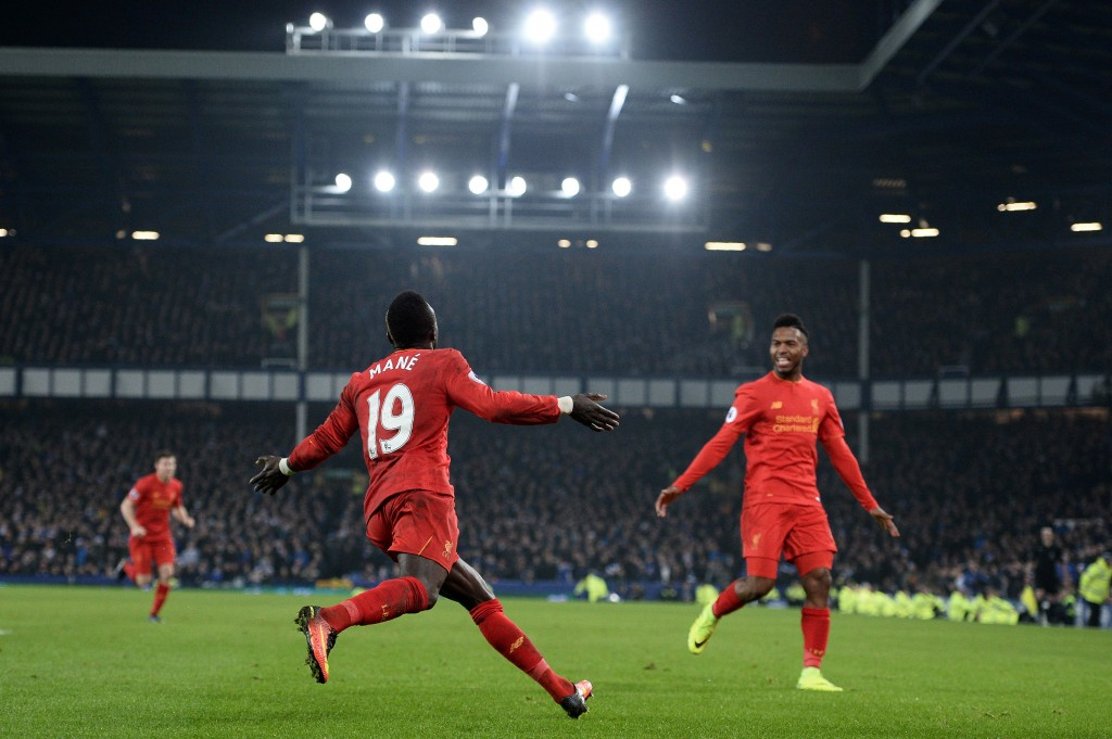 Liverpool's Senegalese midfielder Sadio Mane (C) celebrates scoring his team's first goal with Liverpool's English striker Daniel Sturridge during the English Premier League football match between Everton and Liverpool at Goodison Park in Liverpool, north west England on December 19, 2016. / AFP / Oli SCARFF / RESTRICTED TO EDITORIAL USE. No use with unauthorized audio, video, data, fixture lists, club/league logos or 'live' services. Online in-match use limited to 75 images, no video emulation. No use in betting, games or single club/league/player publications. / (Photo credit should read OLI SCARFF/AFP/Getty Images)