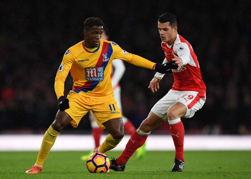 LONDON, ENGLAND - JANUARY 01: Wilfried Zaha of Crystal Palace is challenged by Granit Xhaka of Arsenal during the Premier League match between Arsenal and Crystal Palace at the Emirates Stadium on January 1, 2017 in London, England. (Photo by Shaun Botterill/Getty Images)
