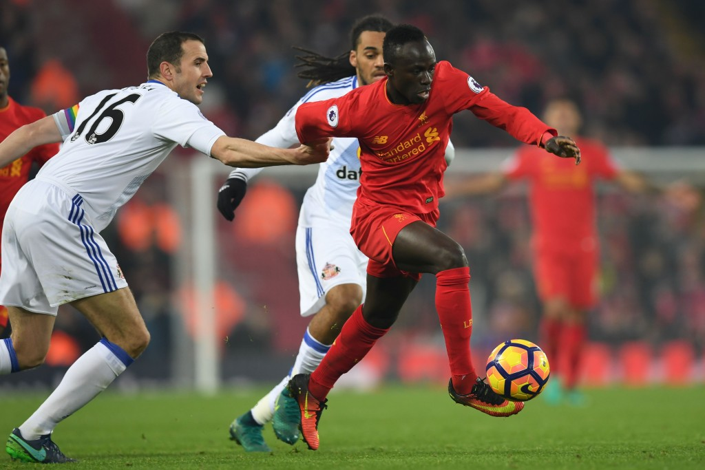 Liverpool's Senegalese midfielder Sadio Mane (R) tries to dribble away from Sunderland's Irish defender John O'Shea (L) during the English Premier League football match between Liverpool and Sunderland at Anfield in Liverpool, north west England on November 26, 2016. / AFP / Paul ELLIS / RESTRICTED TO EDITORIAL USE. No use with unauthorized audio, video, data, fixture lists, club/league logos or 'live' services. Online in-match use limited to 75 images, no video emulation. No use in betting, games or single club/league/player publications. / (Photo credit should read PAUL ELLIS/AFP/Getty Images)