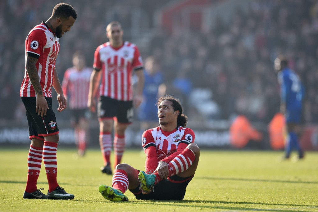 Southampton's Dutch defender Virgil van Dijk (C) sits down injured as Southampton's English defender Ryan Bertrand (L) looks on during the English Premier League football match between Southampton and Leicester City at St Mary's Stadium in Southampton, southern England on January 22, 2017. / AFP / Glyn KIRK / RESTRICTED TO EDITORIAL USE. No use with unauthorized audio, video, data, fixture lists, club/league logos or 'live' services. Online in-match use limited to 75 images, no video emulation. No use in betting, games or single club/league/player publications. / (Photo credit should read GLYN KIRK/AFP/Getty Images)