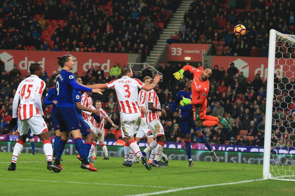 Stoke City's English goalkeeper Lee Grant (R) looks back as he dives to see the ball go into his goal from a free kick hit by Manchester United's English striker Wayne Rooney (L obscured) for Rooney to score an equalising goal for 1-1 and his 250th goal for Manchester United making him the club's all-time record scorer during the English Premier League football match between Stoke City and Manchester United at the Bet365 Stadium in Stoke-on-Trent, central England on January 21, 2017. (Photo by Lindsey Parnaby/AFP/Getty Images)