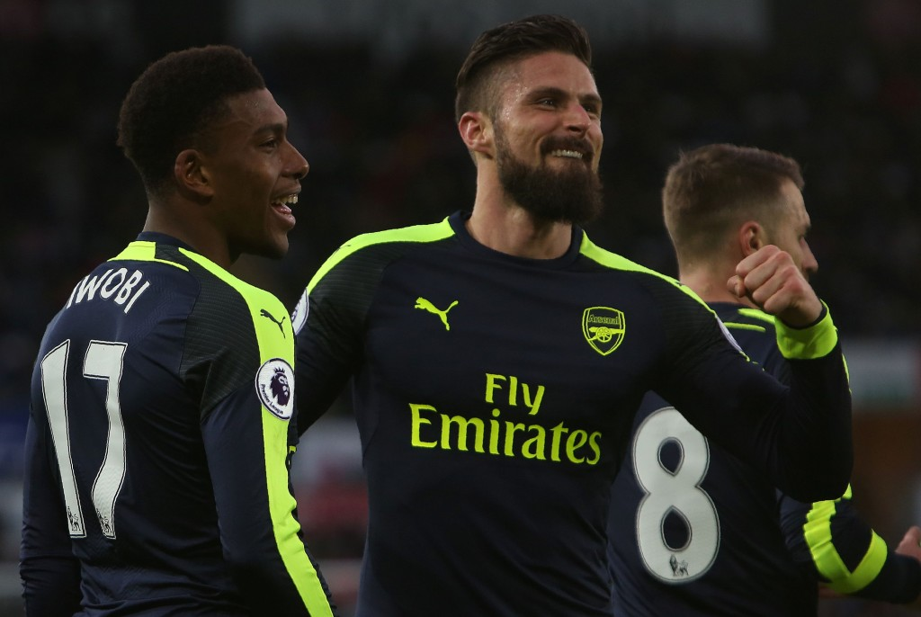 Arsenal's Nigerian striker Alex Iwobi (l) celebrates his team's second goal with Arsenal's French striker Olivier Giroud (C), after his shot was defelected into goal off Swansea City's English midfielder Jack Cork (unseen) during the English Premier League football match between Swansea City and Arsenal at The Liberty Stadium in Swansea, south Wales on January 14, 2017. / AFP / Geoff CADDICK / RESTRICTED TO EDITORIAL USE. No use with unauthorized audio, video, data, fixture lists, club/league logos or 'live' services. Online in-match use limited to 75 images, no video emulation. No use in betting, games or single club/league/player publications. / (Photo credit should read GEOFF CADDICK/AFP/Getty Images)