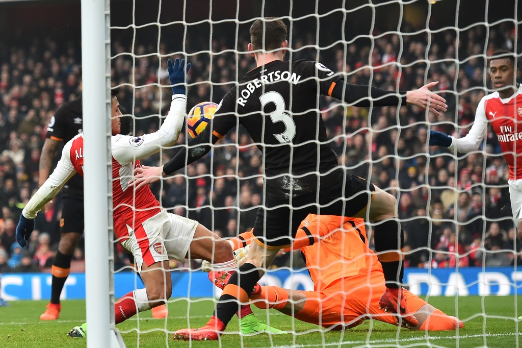 Arsenal's Chilean striker Alexis Sanchez (L) scores the opening goal of the English Premier League football match between Arsenal and Hull City at the Emirates Stadium in London on February 11, 2017. / AFP / Glyn KIRK / RESTRICTED TO EDITORIAL USE. No use with unauthorized audio, video, data, fixture lists, club/league logos or 'live' services. Online in-match use limited to 75 images, no video emulation. No use in betting, games or single club/league/player publications. / (Photo credit should read GLYN KIRK/AFP/Getty Images)