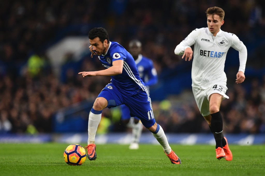 Chelsea's Spanish midfielder Pedro (L) runs with the ball pursued by Swansea City's English midfielder Tom Carroll (R) during the English Premier League football match between Chelsea and Swansea at Stamford Bridge in London on February 25, 2017. / AFP / Glyn KIRK / RESTRICTED TO EDITORIAL USE. No use with unauthorized audio, video, data, fixture lists, club/league logos or 'live' services. Online in-match use limited to 75 images, no video emulation. No use in betting, games or single club/league/player publications. / (Photo credit should read GLYN KIRK/AFP/Getty Images)