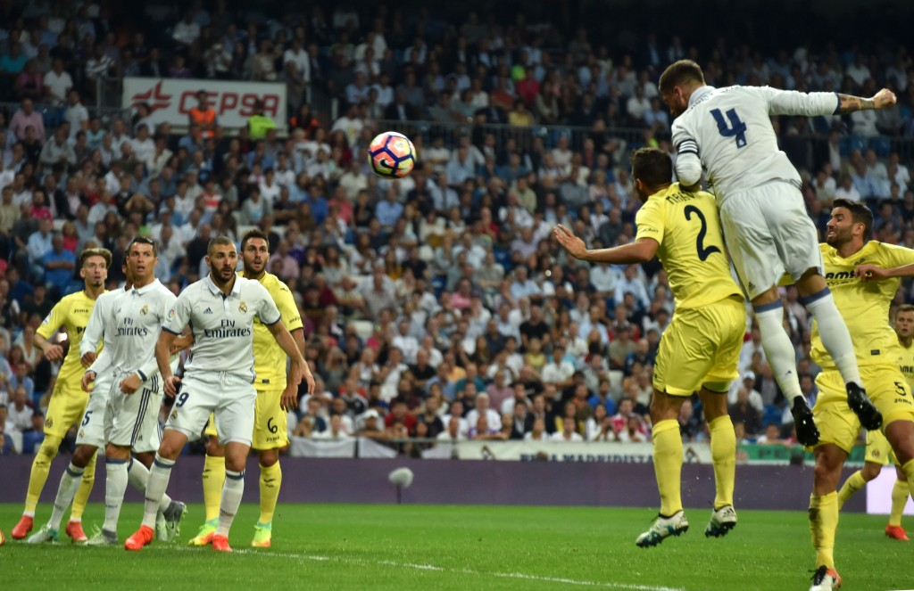 Real Madrid's defender Sergio Ramos (R) heads the ball to score a goal during the Spanish league football match Real Madrid CF vs Villarreal CF at the Santiago Bernabeu stadium in Madrid on September 21, 2016. / AFP / GERARD JULIEN (Photo credit should read GERARD JULIEN/AFP/Getty Images)