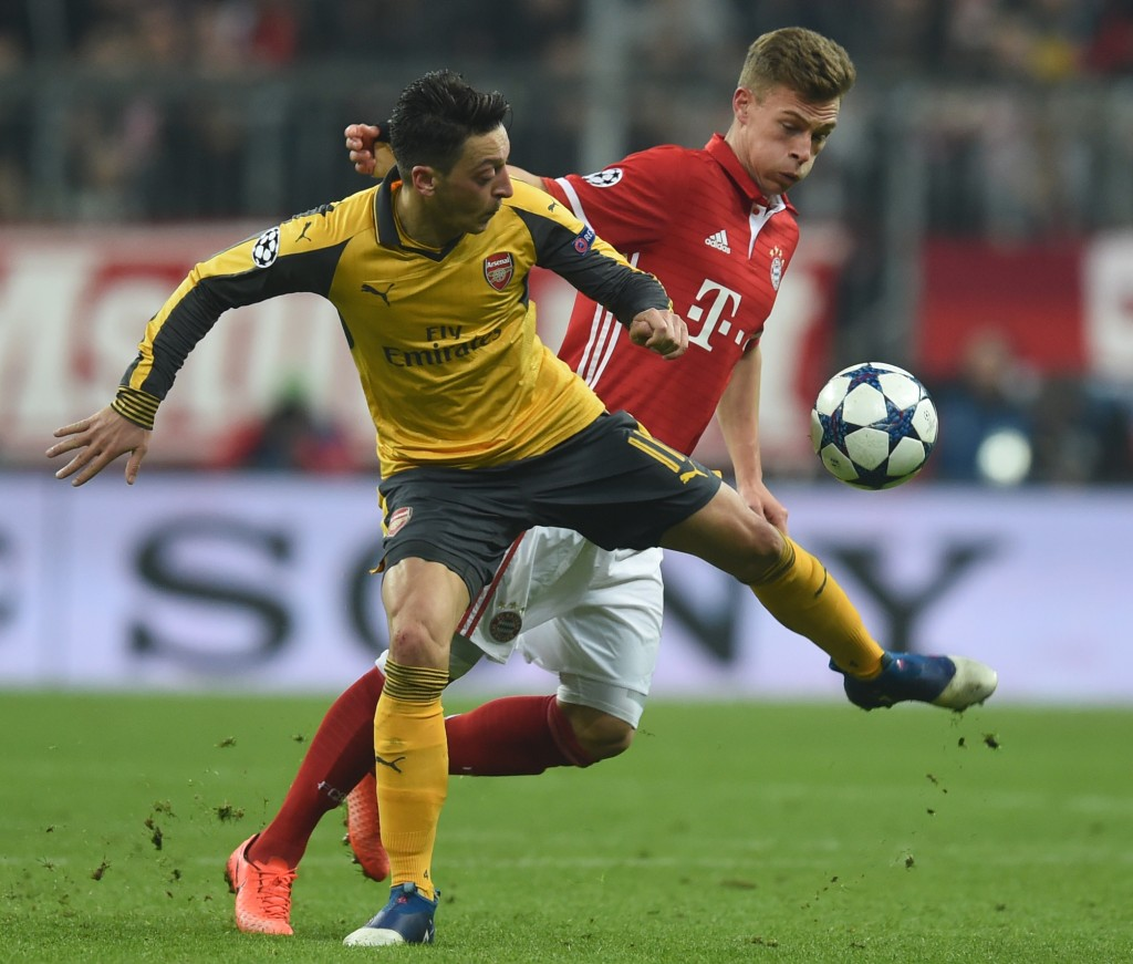 Arsenal's German midfielder Mesut Ozil (L) and Bayern Munich's midfielder Joshua Kimmich (R) vie for the ball during the UEFA Champions League round of sixteen football match between FC Bayern Munich and Arsenal in Munich, southern Germany, on February 15, 2017. / AFP / Christof STACHE (Photo credit should read CHRISTOF STACHE/AFP/Getty Images)