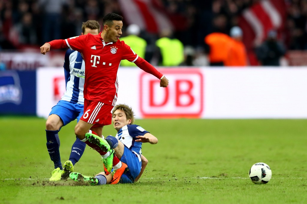 BERLIN, GERMANY - FEBRUARY 18: Genki Haraguchi (R) of Berlin and Thiago of Muenchen battle for the ball during the Bundesliga match between Hertha BSC and Bayern Muenchen at Olympiastadion on February 18, 2017 in Berlin, Germany. (Photo by Martin Rose/Bongarts/Getty Images)