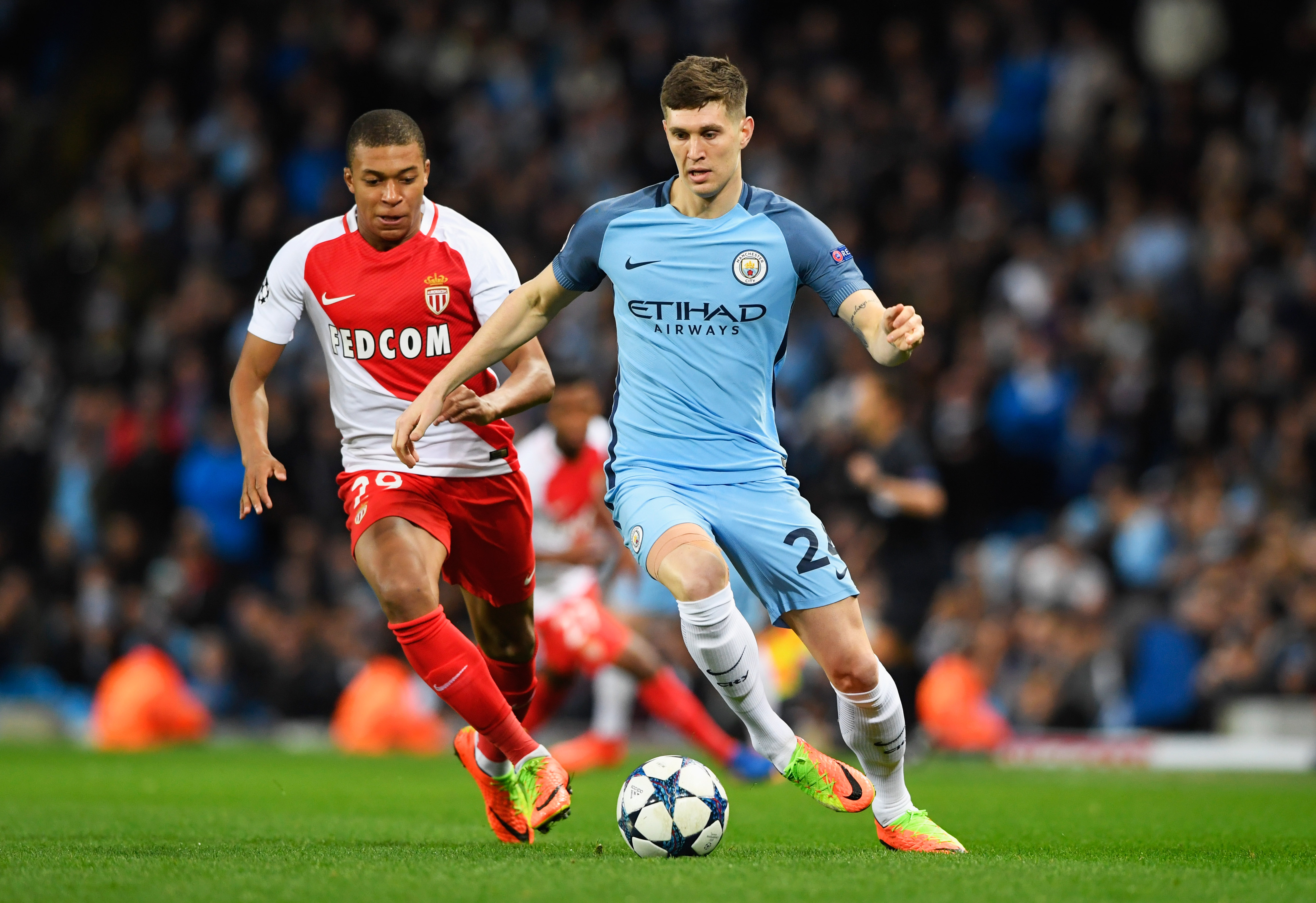 MANCHESTER, ENGLAND - FEBRUARY 21: John Stones of Manchester City is chased by Kylian Mbappe of AS Monaco during the UEFA Champions League Round of 16 first leg match between Manchester City FC and AS Monaco at Etihad Stadium on February 21, 2017 in Manchester, United Kingdom. (Photo by Stu Forster/Getty Images)