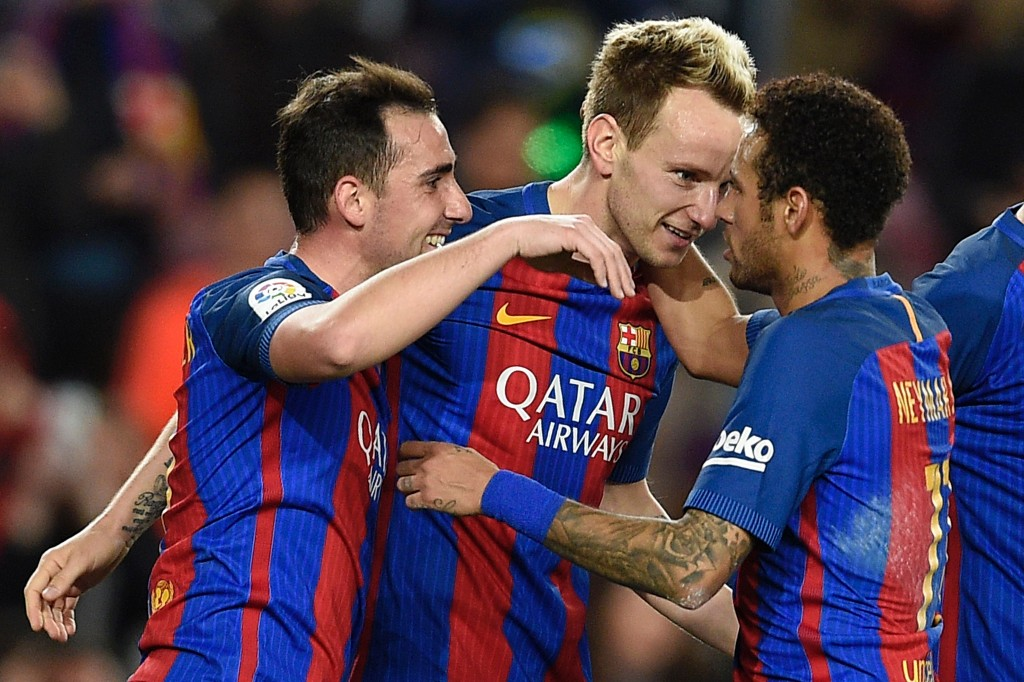 Barcelona's Croatian midfielder Ivan Rakitic (C) celebrates with Barcelona's Brazilian forward Neymar (R) and Barcelona's forward Paco Alcacer after scoring during the Spanish league football match FC Barcelona vs Real Sporting de Gijon at the Camp Nou stadium in Barcelona on March 1, 2017. / AFP PHOTO / LLUIS GENE (Photo credit should read LLUIS GENE/AFP/Getty Images)