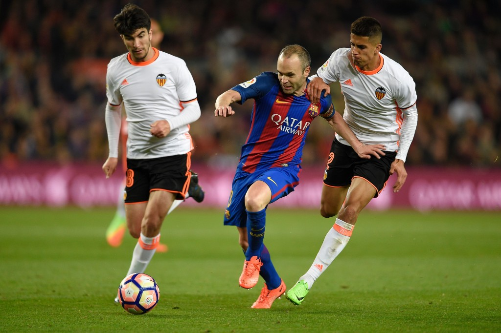 Barcelona's midfielder Andres Iniesta vies with Valencia's Portuguese defender Joao Cancelo (R) and Valencia's Argentinian midfielder Enzo Perez (L) during the Spanish league football match FC Barcelona vs Valencia CF at the Camp Nou stadium in Barcelona on March 19, 2017. / AFP PHOTO / LLUIS GENE (Photo credit should read LLUIS GENE/AFP/Getty Images)
