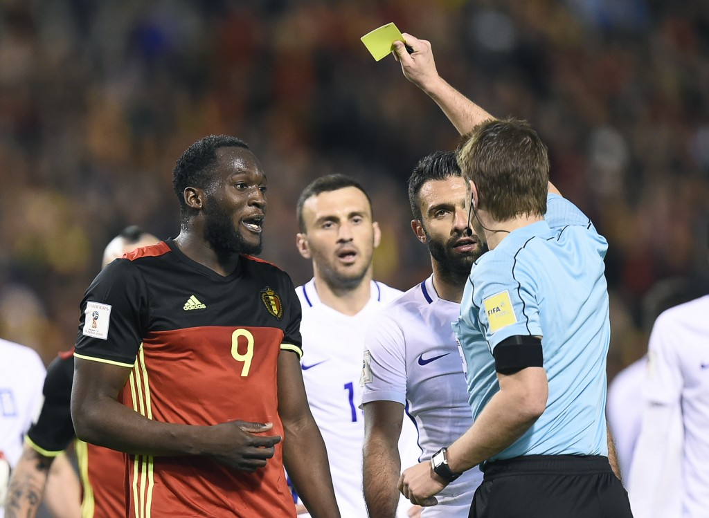 (L to R) Belgium's forward Romelu Lukaku and Greece's Giorgos Tzavellas (2ndR) receive a yellow card from German referee Felix Brych during the FIFA World Cup 2018 qualification football match between Belgium and Greece, at the King Baudouin Stadium, on March 25, 2017 in Brussels. / AFP PHOTO / JOHN THYS (Photo credit should read JOHN THYS/AFP/Getty Images)