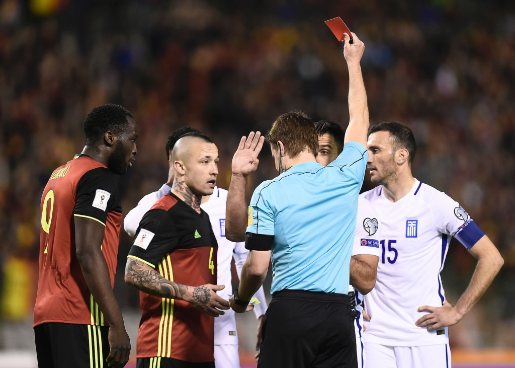 Greece's Giorgos Tzavellas (2nd R) receives a red card from German referee Felix Brych during the FIFA World Cup 2018 qualification football match between Belgium and Greece, at the King Baudouin Stadium, on March 25, 2017 in Brussels. / AFP PHOTO / JOHN THYS (Photo credit should read JOHN THYS/AFP/Getty Images)