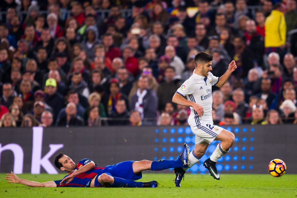 BARCELONA SPAIN- DECEMBER 03 Sergio Busquets of FC Barcelona tackles Marco Asensio of Real Madrid CF during the La Liga match between FC Barcelona and Real Madrid CF at Camp Nou stadium