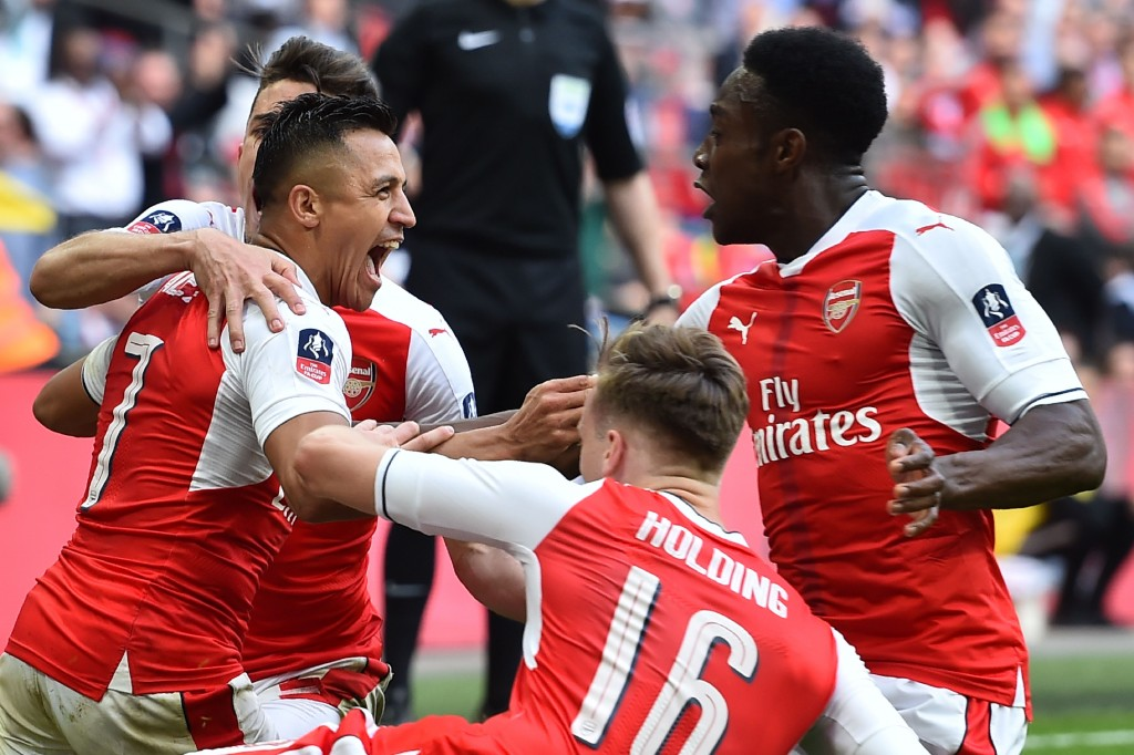 Arsenal's Chilean striker Alexis Sanchez (L) celebrates scoring the second goal with teammates during the FA Cup semi-final football match between Arsenal and Manchester City at Wembley stadium in London on April 23, 2017. / AFP PHOTO / Glyn KIRK / NOT FOR MARKETING OR ADVERTISING USE / RESTRICTED TO EDITORIAL USE (Photo credit should read GLYN KIRK/AFP/Getty Images)