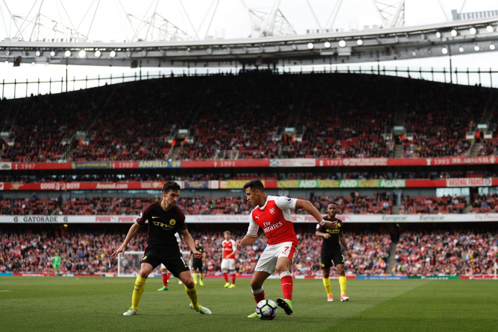 Arsenal's Chilean striker Alexis Sanchez (C) vies with Manchester City's Spanish midfielder Jesus Navas (L) during the English Premier League football match between Arsenal and Manchester City at the Emirates Stadium in London on April 2, 2017. / AFP PHOTO / Adrian DENNIS / RESTRICTED TO EDITORIAL USE. No use with unauthorized audio, video, data, fixture lists, club/league logos or 'live' services. Online in-match use limited to 75 images, no video emulation. No use in betting, games or single club/league/player publications. / (Photo credit should read ADRIAN DENNIS/AFP/Getty Images)