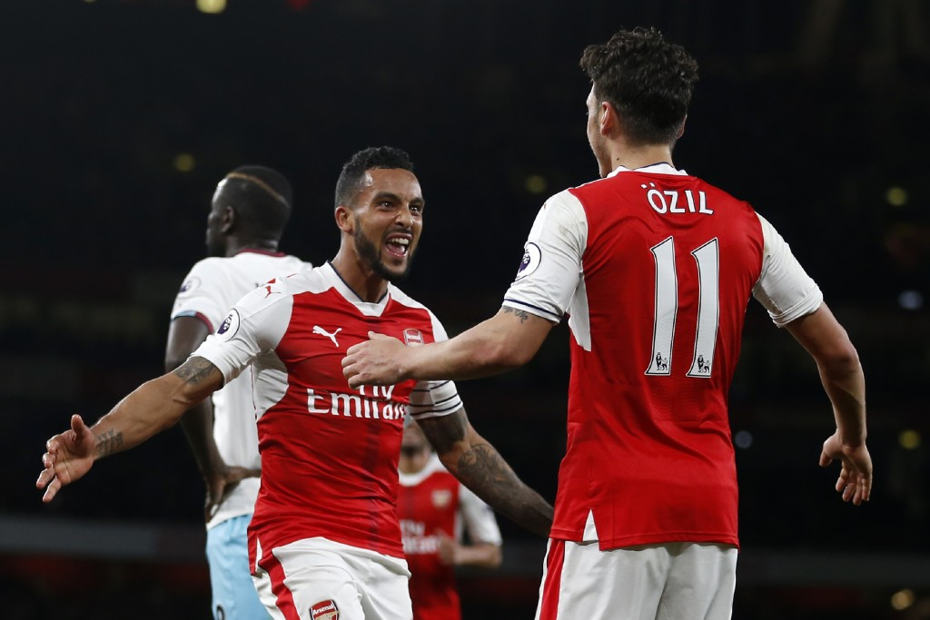 Arsenal's English midfielder Theo Walcott (L) with Mesut Ozil. / AFP PHOTO / Ian KINGTON / RESTRICTED TO EDITORIAL USE. No use with unauthorized audio, video, data, fixture lists, club/league logos or 'live' services. Online in-match use limited to 75 images, no video emulation. No use in betting, games or single club/league/player publications. / (Photo credit should read IAN KINGTON/AFP/Getty Images)