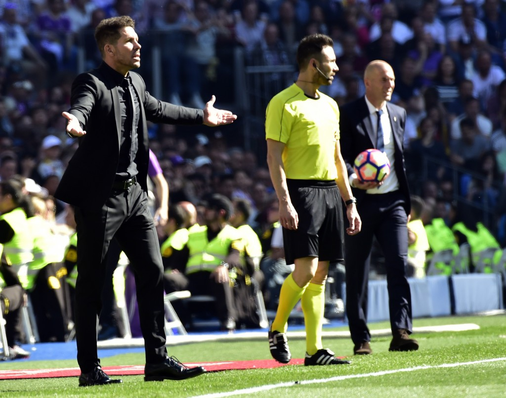 Atletico Madrid's Argentinian coach Diego Simeone (L) gestures close to Real Madrid's French coach Zinedine Zidane during the Spanish league football match Real Madrid CF vs Club Atletico de Madrid at the Santiago Bernabeu stadium in Madrid on April, 8, 2017. / AFP PHOTO / GERARD JULIEN (Photo credit should read GERARD JULIEN/AFP/Getty Images)