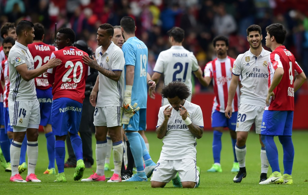 Real Madrid's Brazilian defender Marcelo (C) kneels at the end of the Spanish league football match Real Sporting de Gijon vs Real Madrid CF at El Molinon stadium in Gijon on April 15, 2017. / AFP PHOTO / MIGUEL RIOPA (Photo credit should read MIGUEL RIOPA/AFP/Getty Images)