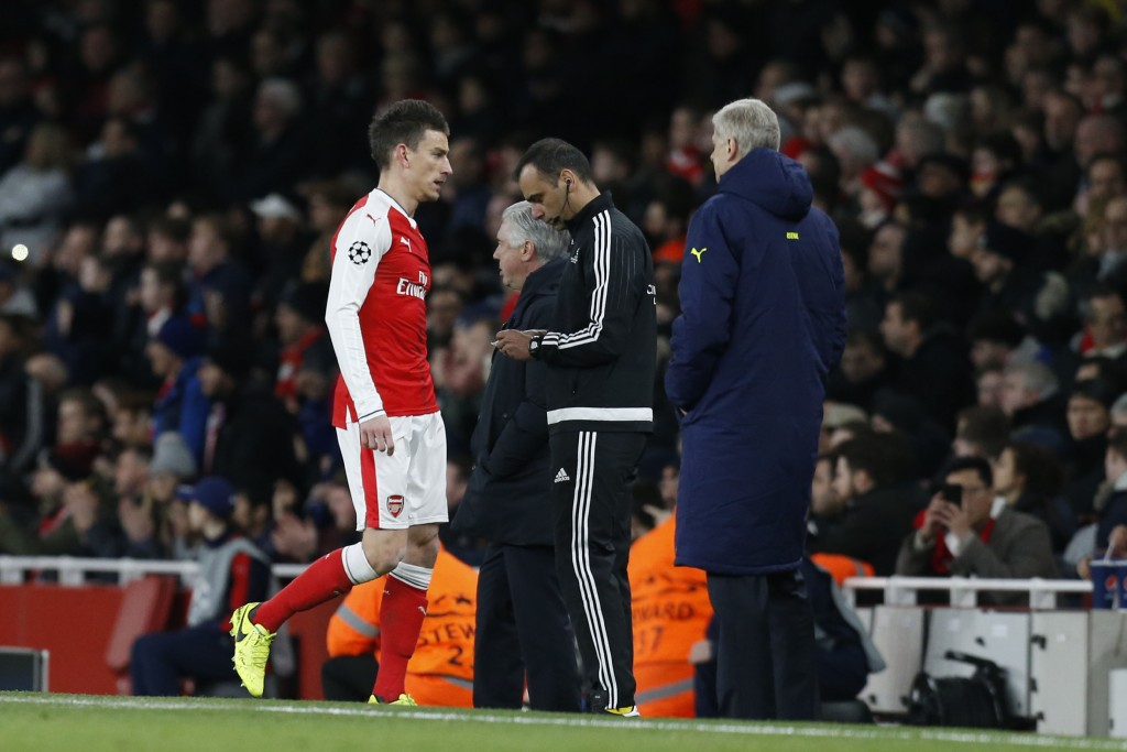 Arsenal's French defender Laurent Koscielny (L) leaves the pitch after being given a red card during the UEFA Champions League last 16 second leg football match between Arsenal and Bayern Munich at The Emirates Stadium in London on March 7, 2017. / AFP PHOTO / IKIMAGES / Ian KINGTON (Photo credit should read IAN KINGTON/AFP/Getty Images)