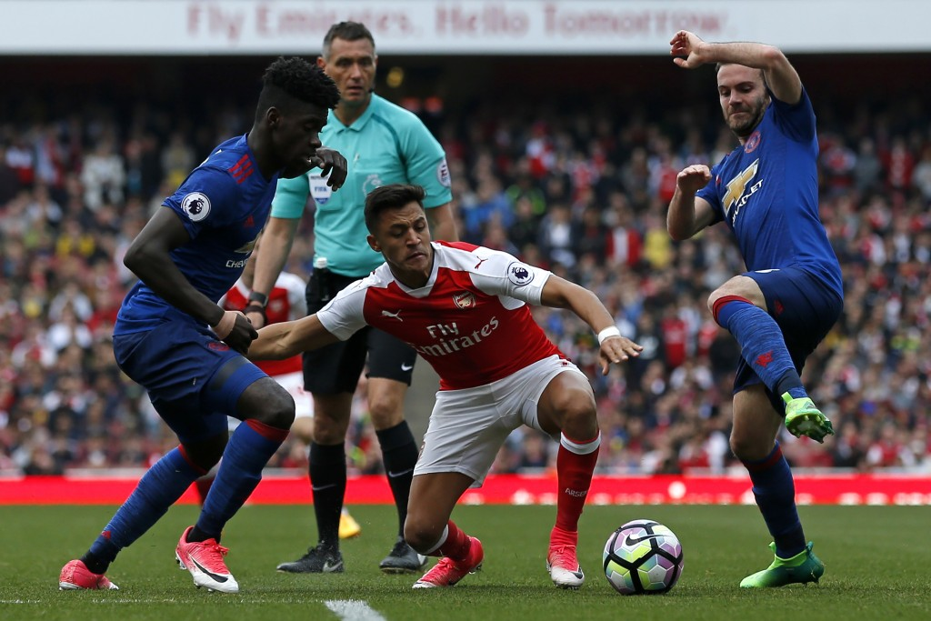 Arsenal's Chilean striker Alexis Sanchez (C) vies with Manchester United's DR Congo-born defender Axel Tuanzebe (L) and Manchester United's Spanish midfielder Juan Mata (R) during the English Premier League football match between Arsenal and Manchester United at the Emirates Stadium in London on May 7, 2017. Arsenal won the game 2-0. / AFP PHOTO / IKIMAGES / Ian KINGTON / RESTRICTED TO EDITORIAL USE. No use with unauthorized audio, video, data, fixture lists, club/league logos or 'live' services. Online in-match use limited to 45 images, no video emulation. No use in betting, games or single club/league/player publications. / (Photo credit should read IAN KINGTON/AFP/Getty Images)
