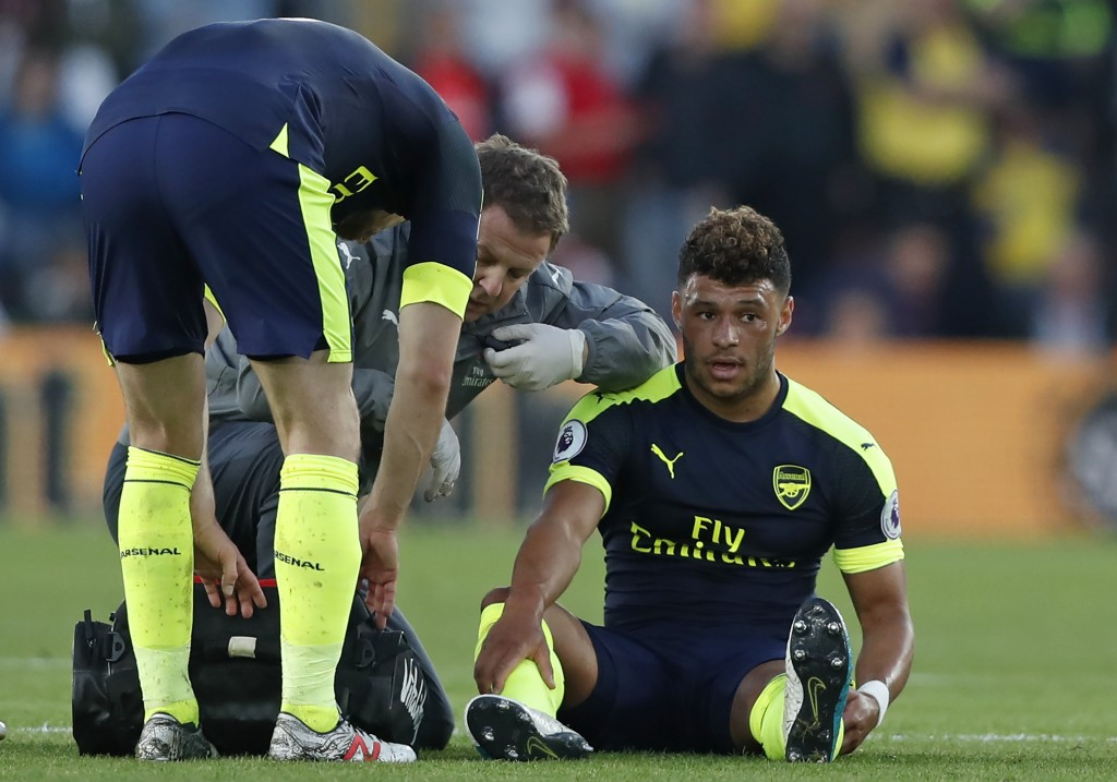 Arsenal's English midfielder Alex Oxlade-Chamberlain (R) receives medical attention after picking up an injury during the English Premier League football match between Southampton and Arsenal at St Mary's Stadium in Southampton, southern England on May 10, 2017. / AFP PHOTO / Adrian DENNIS / RESTRICTED TO EDITORIAL USE. No use with unauthorized audio, video, data, fixture lists, club/league logos or 'live' services. Online in-match use limited to 75 images, no video emulation. No use in betting, games or single club/league/player publications. / (Photo credit should read ADRIAN DENNIS/AFP/Getty Images)