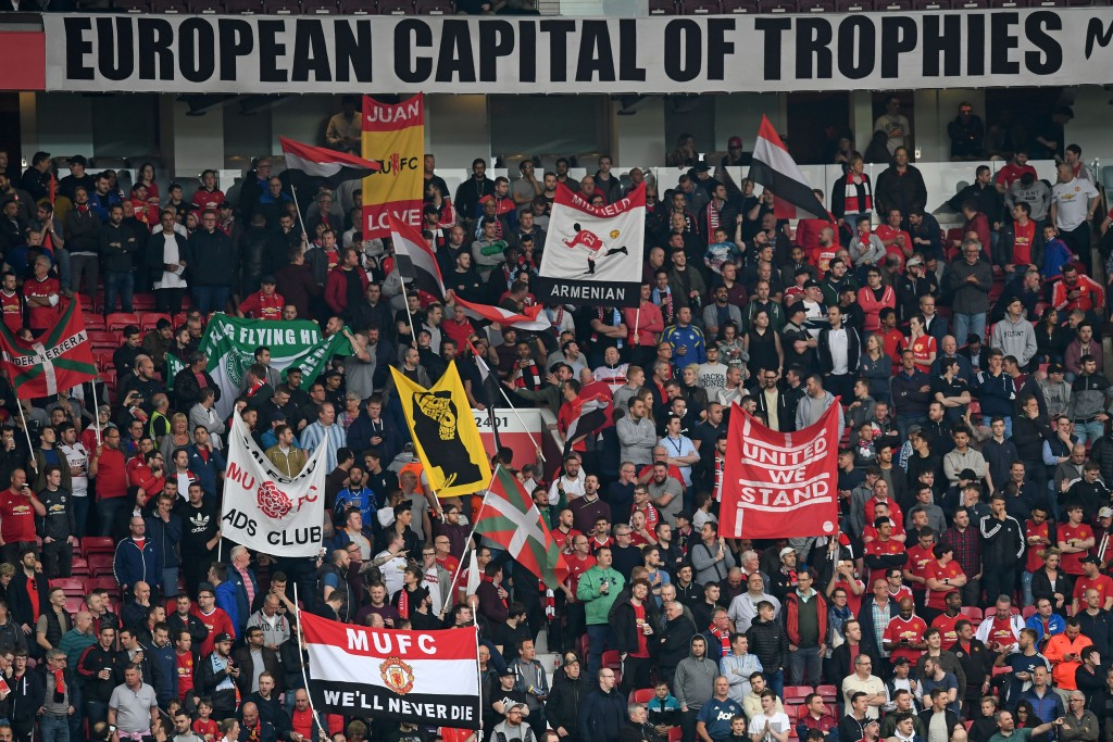 Manchester United supporters hold up banners in the crowd ahead of the UEFA Europa League semi-final, second-leg football match between Manchester United and Celta Vigo at Old Trafford stadium in Manchester, north-west England, on May 11, 2017. / AFP PHOTO / Paul ELLIS (Photo credit should read PAUL ELLIS/AFP/Getty Images)