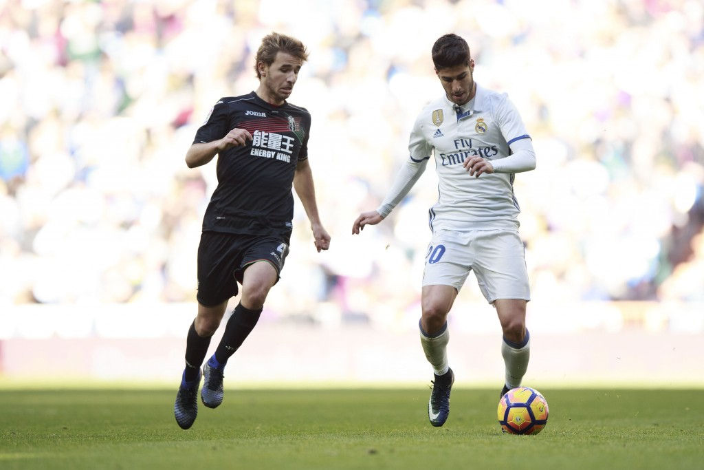 MADRID, SPAIN - JANUARY 07: Marco Asensio (R) of Real Madrid CF competes for the ball with Sergi Samper (L) of Granada CF during the La Liga match between Real Madrid CF and Granada CF at Estadio Santiago Bernabeu on January 7, 2017 in Madrid, Spain. (Photo by Gonzalo Arroyo Moreno/Getty Images)