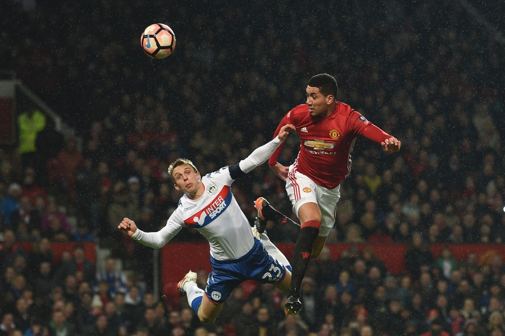 Manchester United's English defender Chris Smalling (R) heads the ball in to score their second goal during the English FA Cup fourth round football match between Manchester United and Wigan Athletic at Old Trafford in Manchester, north west England, on January 29, 2017. / AFP / Paul ELLIS / RESTRICTED TO EDITORIAL USE. No use with unauthorized audio, video, data, fixture lists, club/league logos or 'live' services. Online in-match use limited to 75 images, no video emulation. No use in betting, games or single club/league/player publications. / (Photo credit should read PAUL ELLIS/AFP/Getty Images)