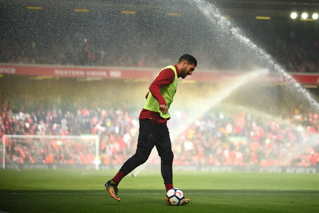 Liverpool's German midfielder Emre Can warms up as the pitch is watered at half time in the English Premier League football match between Liverpool and Crystal Palace at Anfield in Liverpool, north west England on August 19, 2017. / AFP PHOTO / Oli SCARFF / RESTRICTED TO EDITORIAL USE. No use with unauthorized audio, video, data, fixture lists, club/league logos or 'live' services. Online in-match use limited to 75 images, no video emulation. No use in betting, games or single club/league/player publications. / (Photo credit should read OLI SCARFF/AFP/Getty Images)