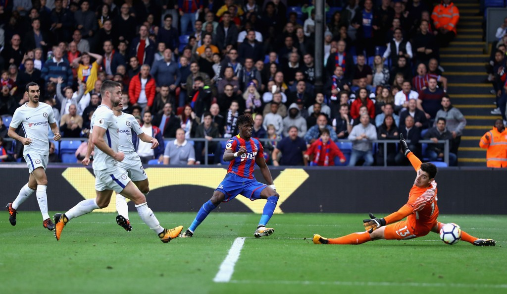 LONDON, ENGLAND - OCTOBER 14: Wilfried Zaha of Crystal Palace scores his sides second goal past Thibaut Courtois of Chelsea during the Premier League match between Crystal Palace and Chelsea at Selhurst Park on October 14, 2017 in London, England. (Photo by Dan Istitene/Getty Images)