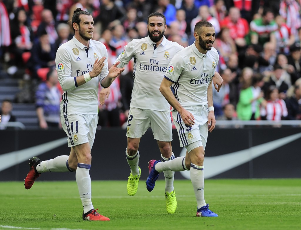 Real Madrid's French forward Karim Benzema (R) celebrates with teammates Welsh forward Gareth Bale (L) and defender Daniel Carvajal (C) after scoring their team's first goal during the Spanish league football match Athletic Club Bilbao vs Real Madrid CF at the San Mames stadium in Bilbao on March 18, 2017. / AFP PHOTO / ANDER GILLENEA (Photo credit should read ANDER GILLENEA/AFP/Getty Images)