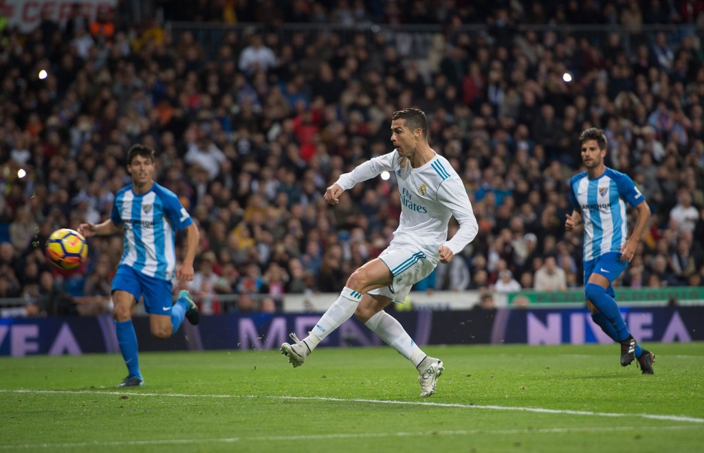 MADRID, SPAIN - NOVEMBER 25: Cristiano Ronaldo of Real Madrid CF scores his team's 3rd goal from a penalty rebound during the La Liga match between Real Madrid and Malaga at Estadio Santiago Bernabeu on November 25, 2017 in Madrid, Spain. (Photo by Denis Doyle/Getty Images)