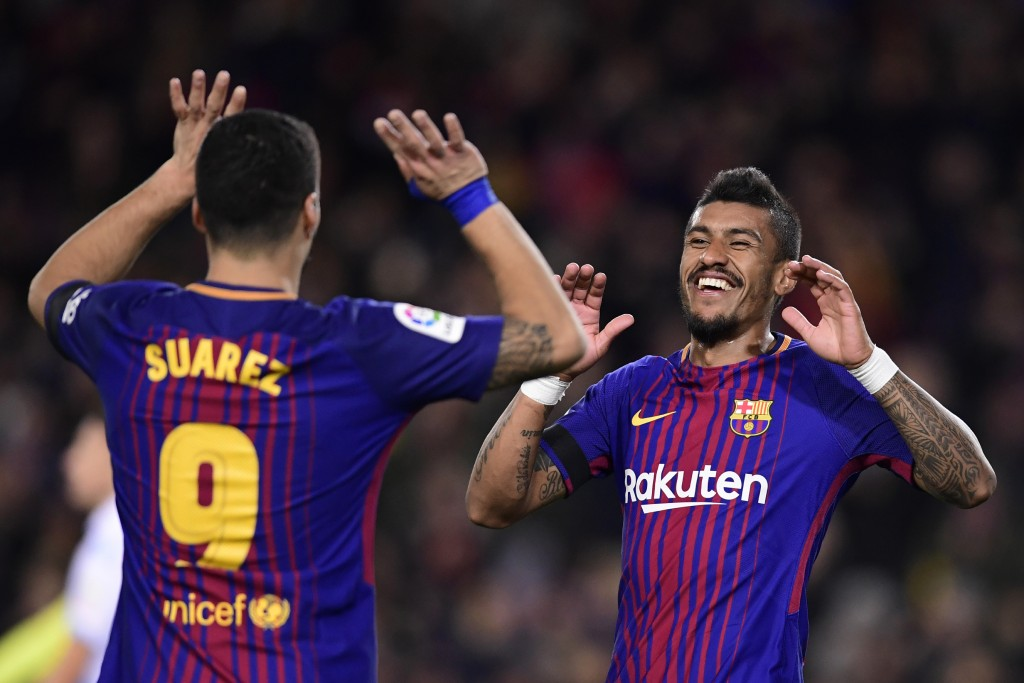Barcelona's Brazilian midfielder Paulinho celebrates with Barcelona's Uruguayan forward Luis Suarez after scoring during the Spanish league football match FC Barcelona against RC Deportivo de la Coruna at the Camp Nou stadium in Barcelona on December