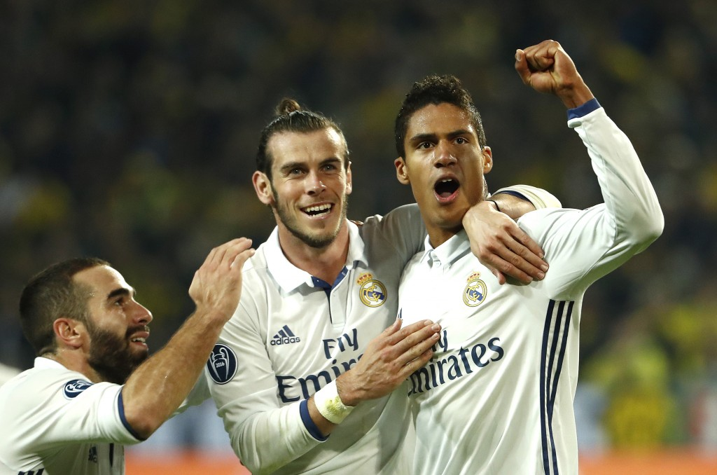 Real Madrid's French defender Raphael Varane (R) reacts after scoring with Real Madrid's Welsh forward Gareth Bale (c) during the UEFA Champions League first leg football match between Borussia Dortmund and Real Madrid at BVB stadium in Dortmund, on September 27, 2016. / AFP / Odd ANDERSEN (Photo credit should read ODD ANDERSEN/AFP/Getty Images)