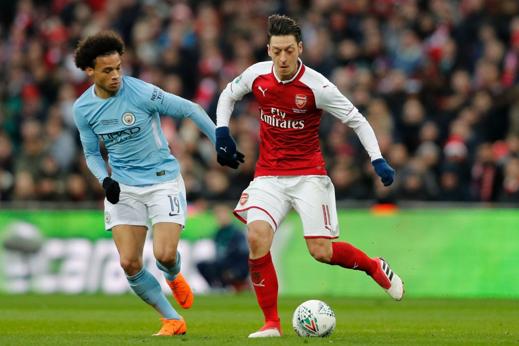 Manchester City's German midfielder Leroy Sane (L) vies with Arsenal's German midfielder Mesut Ozil during the English League Cup final football match between Manchester City and Arsenal at Wembley stadium in north London on February 25, 2018. / AFP PHOTO / Adrian DENNIS / RESTRICTED TO EDITORIAL USE. No use with unauthorized audio, video, data, fixture lists, club/league logos or 'live' services. Online in-match use limited to 75 images, no video emulation. No use in betting, games or single club/league/player publications. / (Photo credit should read ADRIAN DENNIS/AFP/Getty Images)