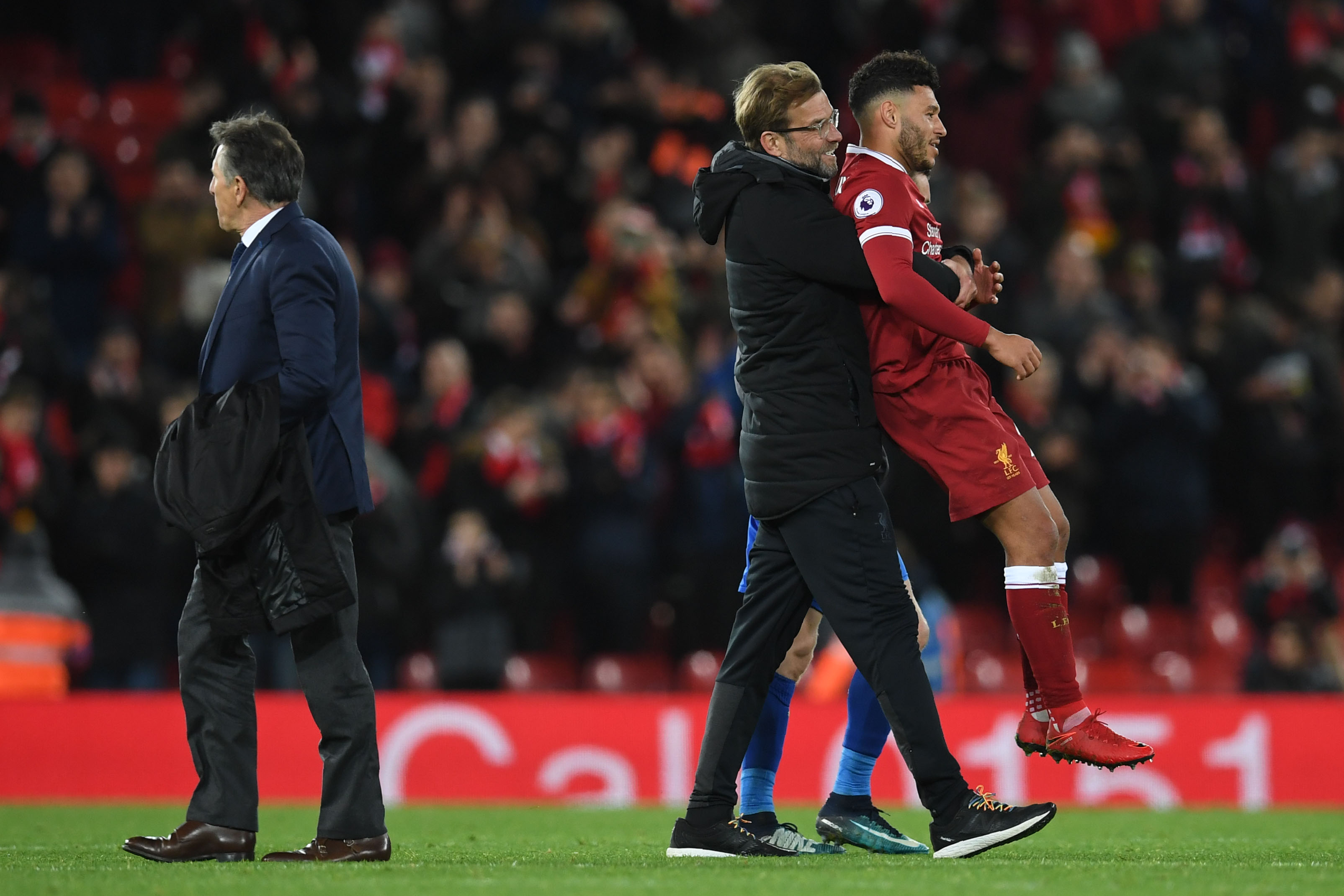 Liverpool's German manager Jurgen Klopp (C) congratulates Liverpool's English midfielder Alex Oxlade-Chamberlain (R) as Leicester City's French manager Claude Puel walks after the English Premier League football match between Liverpool and Leicester at Anfield in Liverpool, north west England on December 30, 2017. / AFP PHOTO / Paul ELLIS / RESTRICTED TO EDITORIAL USE. No use with unauthorized audio, video, data, fixture lists, club/league logos or 'live' services. Online in-match use limited to 75 images, no video emulation. No use in betting, games or single club/league/player publications. / (Photo credit should read PAUL ELLIS/AFP/Getty Images)