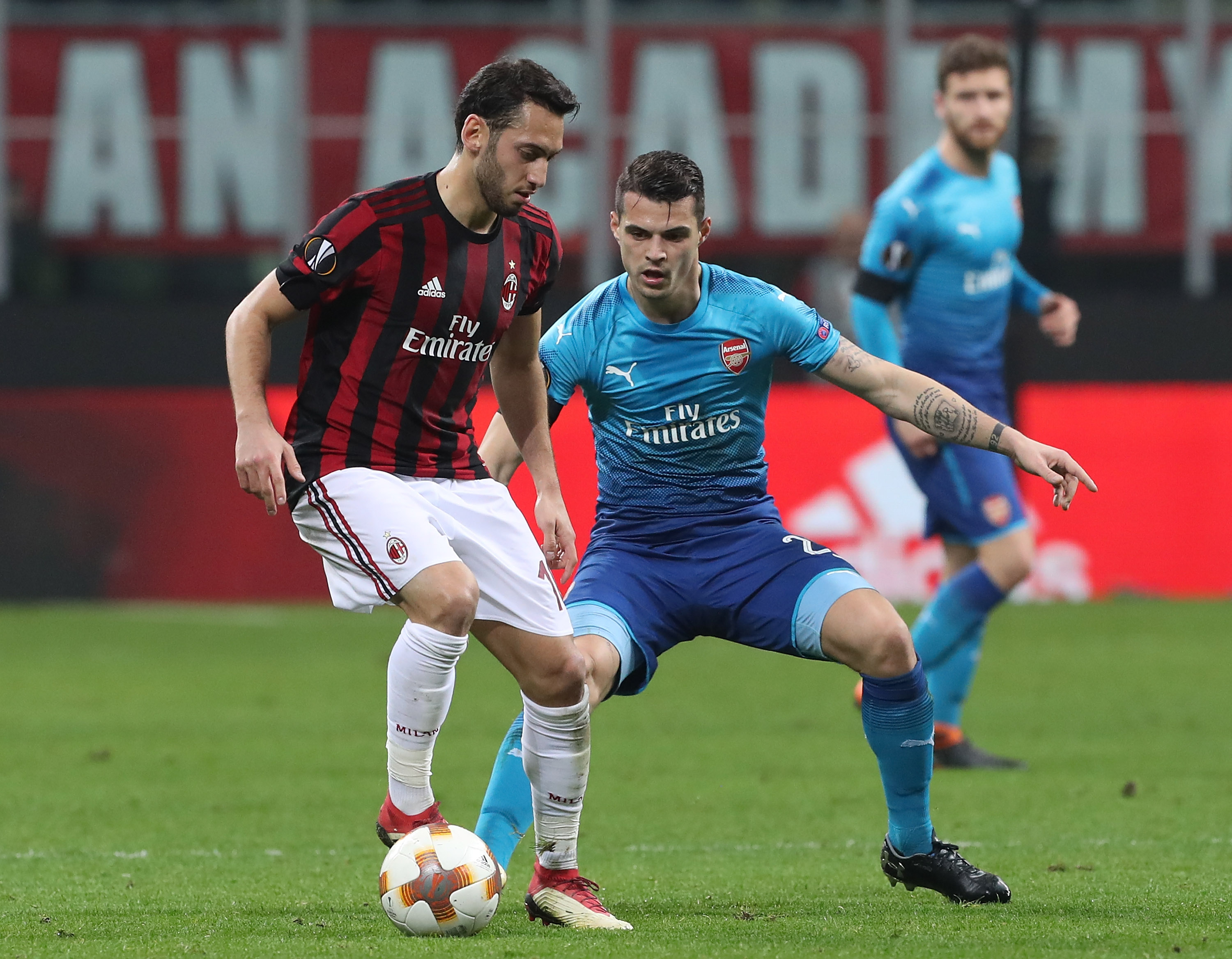 MILAN, ITALY - MARCH 08: Hakan Calhanoglu of AC Milan competes for the ball withGranit Xhaka of Arsenal during UEFA Europa League Round of 16 match between AC Milan and Arsenal at the San Siro on March 8, 2018 in Milan, Italy. (Photo by Marco Luzzani/Getty Images)