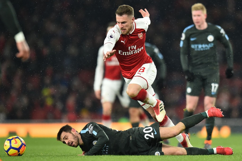 Arsenal's Welsh midfielder Aaron Ramsey (C) vies with Manchester City's Portuguese midfielder Bernardo Silva during the English Premier League football match between Arsenal and Manchester City at the Emirates Stadium in London on March 1, 2018. / AFP PHOTO / Glyn KIRK / RESTRICTED TO EDITORIAL USE. No use with unauthorized audio, video, data, fixture lists, club/league logos or 'live' services. Online in-match use limited to 75 images, no video emulation. No use in betting, games or single club/league/player publications. / (Photo credit should read GLYN KIRK/AFP/Getty Images)