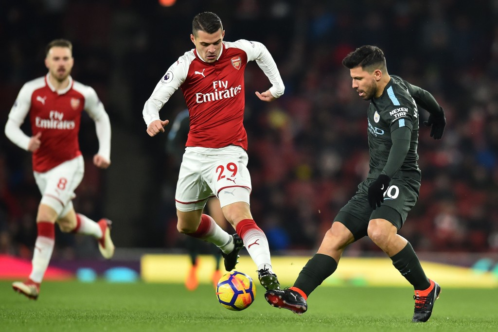 Manchester City's Argentinian striker Sergio Aguero (R) vies with Arsenal's Swiss midfielder Granit Xhaka (C) during the English Premier League football match between Arsenal and Manchester City at the Emirates Stadium in London on March 1, 2018. / AFP PHOTO / Glyn KIRK / RESTRICTED TO EDITORIAL USE. No use with unauthorized audio, video, data, fixture lists, club/league logos or 'live' services. Online in-match use limited to 75 images, no video emulation. No use in betting, games or single club/league/player publications. / (Photo credit should read GLYN KIRK/AFP/Getty Images)
